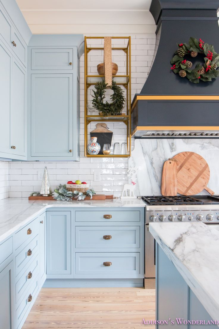 Inside Our Vintage Modern Style Holiday Kitchen with HomeGoods... Sponsored by HomeGoods.  kitchen-powder-blue-gray-cabinet-color-white-marble-countertops-calcutta-gold-black-barstools-vent-hood-gold-trim-modern-vintage-open-shelving-antique-brass-cup-pull-knob-whitewashed-hardwood-flooring-long-white-subway-tile-backsplash-scalloped-marble-piece-behind-stove