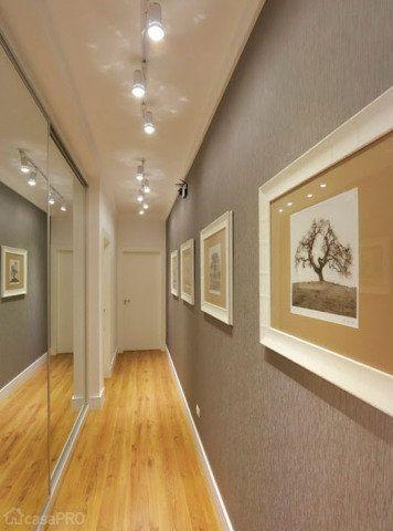 Para ampliar mais o espaço, espelhos foram aplicados nas portas do roupeiro, proporcionando a sensação de um corredor mais largo. Do outro lado, um papel de parede texturizado na cor cinza e para finalizar, uma galeria de gravuras. A iluminação é composta por um trilho eletrificado, com lâmpadas de PAR20, que além de iluminar, destaca a galeria de quadros. Projeto de Simo