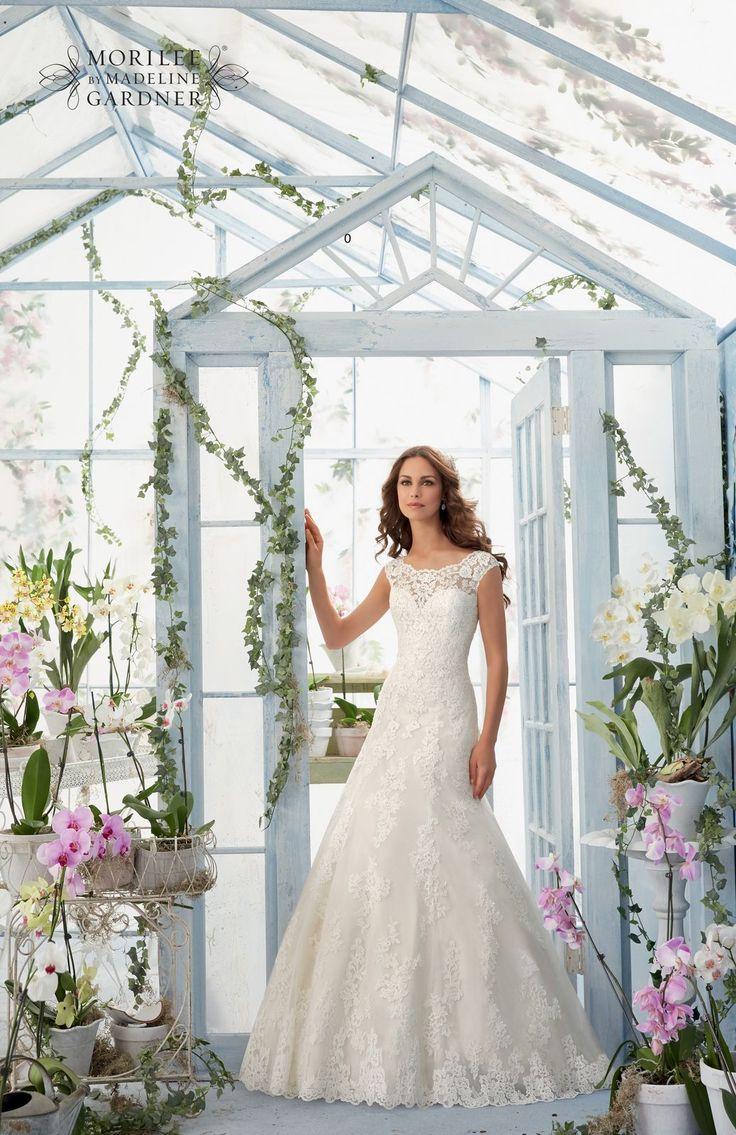 Romantyczna koronkowa suknia ślubna Mori Lee z kolekcji BLU. Dekolt w kształcie łódki, piękne haftowane kwiatowe wzory na półprzeźroczystym tiulu …