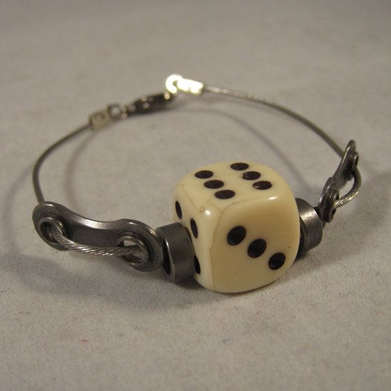 This bracelet is made from a recycled bike shifter cable with bike chain links and bearings/rollers surrounding a bone color die. The bracelet measures 7 long (will fit up to 6-1/2 wrist) and closes with a gunmetal lobster clasp. If a different length is desired, please include instructions with your order.