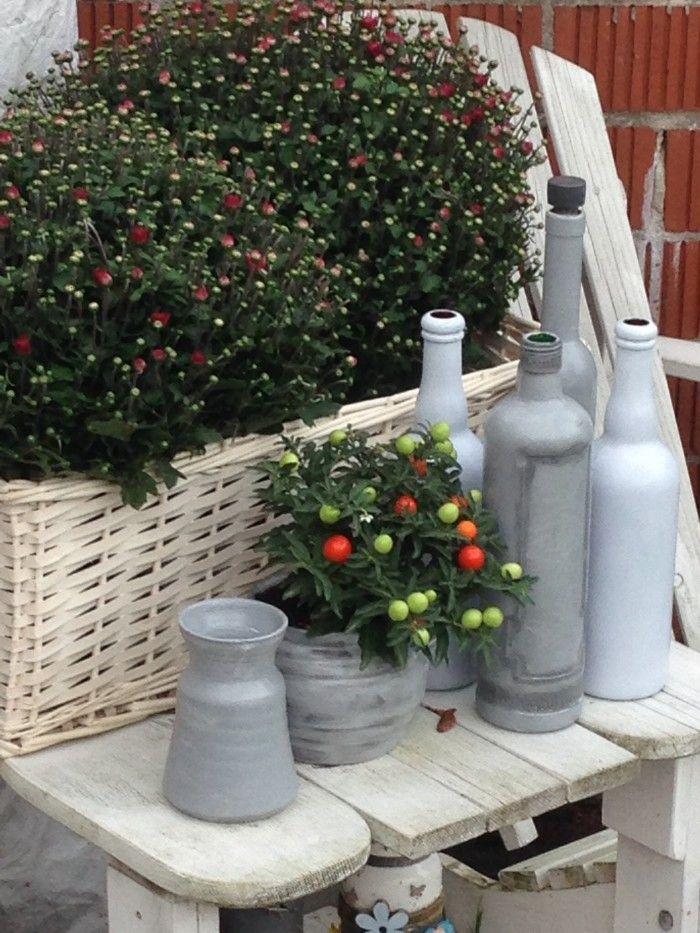 Herfst in hoekje van de tuin. Potte en flessen zelf beschilderd
