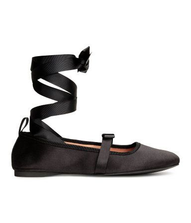 Black. Satin ballet flats with attached bow over the foot, grosgrain trim at top, and wide grosgrain ribbons that tie around ankle. Satin lining, imitation