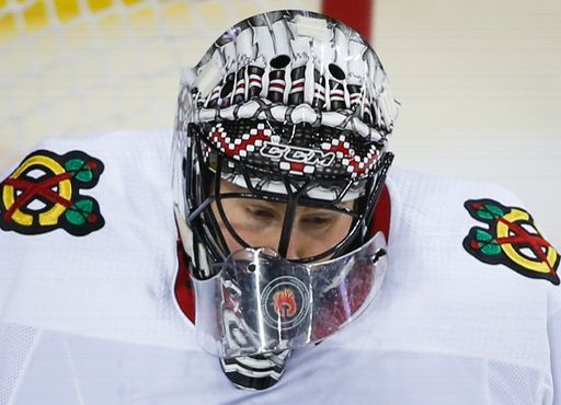 Chicago Blackhawks goalie Jeff Glass has a shot from the Calgary Flames get under his neck guard during the first period of an NHL hockey game Sunday, Dec. 31, 2017, in Calgary, Alberta. (Jeff McIntosh/The Canadian Press via AP)