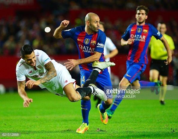 Sevilla's midfielder Vitolo falls past Barcelona's Argentinian defender Javier Mascherano during the Spanish league football match Sevilla FC vs FC...