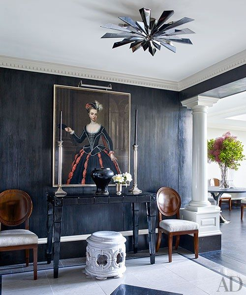 A Tony Duquette fixture by Remains Lighting crowns the opened-up entrance hall, where an 18th-century portrait by Thomas Gibson surmounts a Baccarat console | archdigest.com