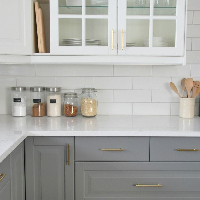A Grey And White Kitchen Featuring A White Subway Tile