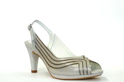 Sandalia vestir/ceremonia de la marca argenta, piel luce color plata, ribetes metálicos color acero, destalonada y punta abierta, cierre con hebilla