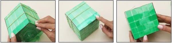 ) Você vai precisar de tesoura, alicate, fita crepe, quatro garrafas PET cortadas em tiras de 2cm de largura, elásticos e um molde de 10x10x10cm  2) Corte uma tira em um comprimento que permita cobrir dois lados mais o fundo da caixa, deixando ainda 4cm de sobra em cada ponta  3) Ajuste a fita ao molde, cobrindo dois lados e o fundo. Vinque as sobras de 4cm para facilitar o trabalho    4) Passe elásticos em torno do molde a fim de fixar melhor as fitas  5) Corte mais quatro fitas e…