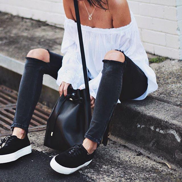 off shoulder white top, ripped black denim, black platform sneakers, black bucket bag