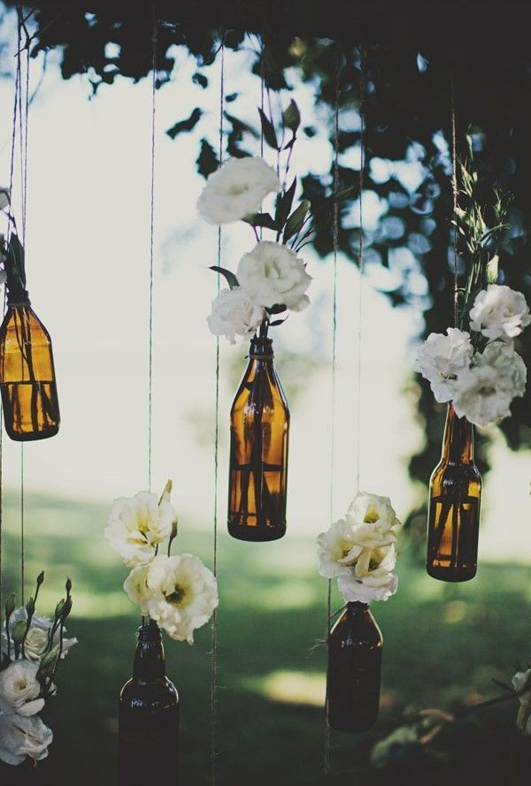 Hang your flower arrangements in mason jars or glass bottles above your tablescape. Not only does it save room on your table, it makes for a chic idea for a rustic wedding.