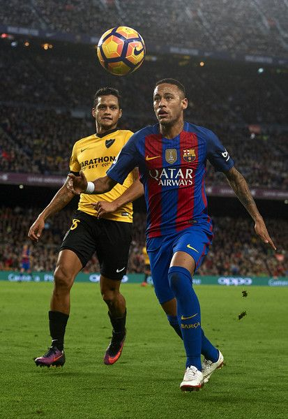 Neymar JR of Barcelona competes for the ball with Roberto Rosales (L) of Malaga during the La Liga match between FC Barcelona and Malaga CF at Camp Nou stadium on November 19, 2016 in Barcelona, Spain.