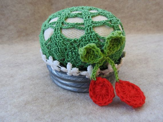 Altered Art Up Cycled Pincushion made from a vintage zinc Ball canning jar lid with a batting stuffed green crocheted doily. The pincushion is embellished with a vintage red cherry applique and flower trim. The pincushion is about 2.5 inches tall and 3 inches in diameter. Great
