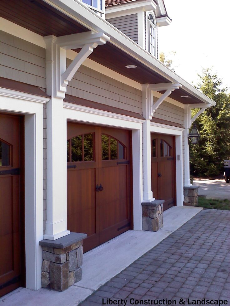 Rustic 3-car garage with half rounded windows above. The average price to install a new garage door is $964.