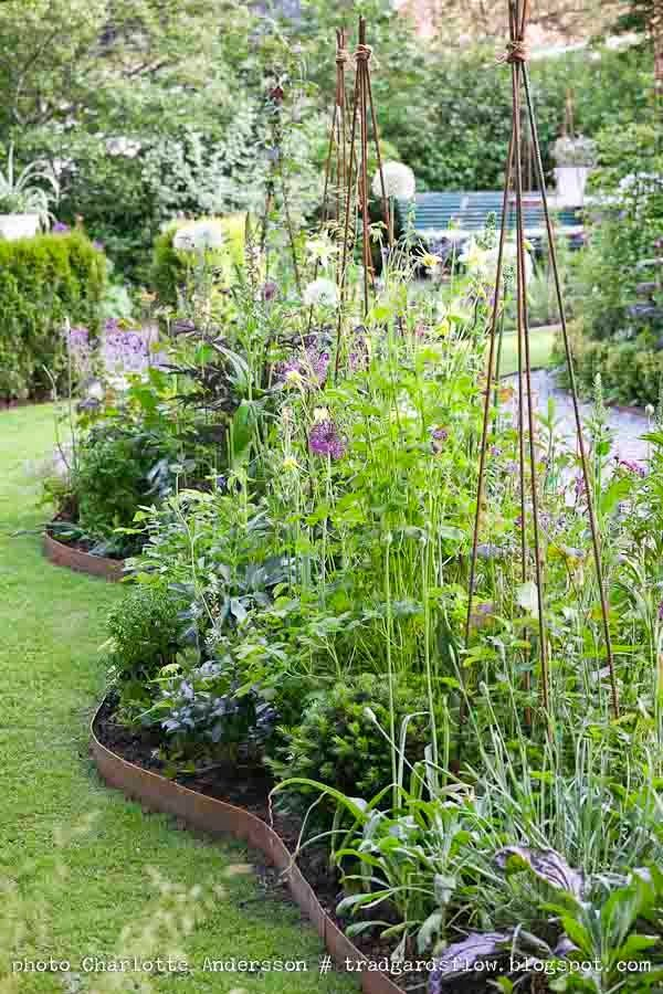 Love this,  organic border and trellises with various lavender plants.