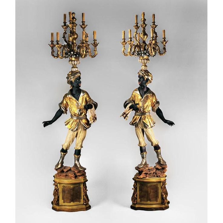 Hand Carved Polychromed Italian Blackamoor Torchieres ~ A highly decorative pair of matching right and left Italian Blackamoor Torchieres, each mounted with an electrified nine-light candelabra, each facing the other on a rusticated perch of rocks atop a pedestal base. They stand with towel in hand ready to serve and are exquisitely decorated in gold and silver leaf applied over a polychrome finish.