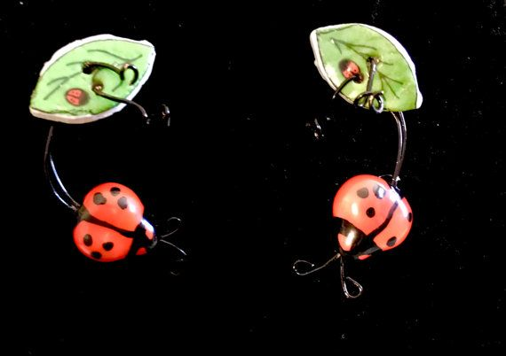 Cherry Red and black, Love Bug stud style earrings. Ladybug earrings, fun jewelry to gift for your Sweetheart, Mom or a July Birthday. Perhaps a perfect retirement gift for an avid gardener. Nickel free earring posts. Just like nature, this pair of drop style earrings is designed to be similar but not identical. Earring Details - drop style earrings on posts * Ceramic Ladybugs (about .75 inches / 2 cm) * Ceramic leaves (about 1 inches / 3 cm long) * black wire wrapping - each earrin...