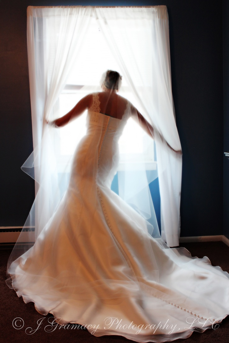 Bride in wedding gown illuminated by window light