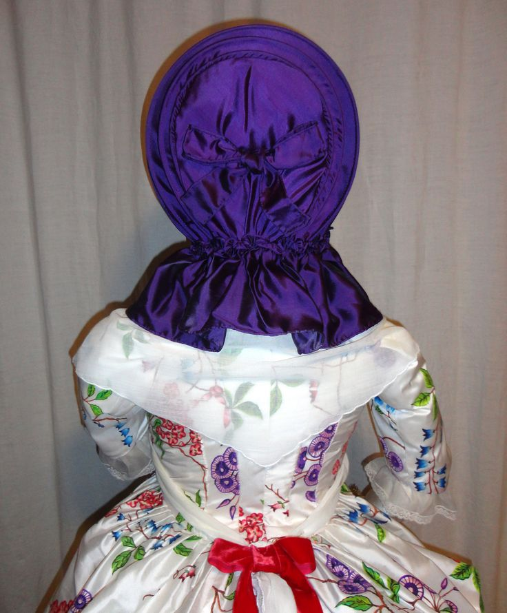 Back view of the figure. Like many original calashes, this purple silk version has a pretty bow ornamenting the back panel. Entirely hand-sewn, it features wicker canes to create the unique bow shape which characterizes the style, and has a gathered shoulder-cape and silk ribbons. . The fine cotton kerchief is over 75 inches long; it goes over the shoulders, crosses in front and is tied at the back waistline, where a rose-red ribbon also serves as an accent to the poufed polonaise…