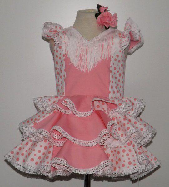 Traje de gitana para niña en popelín blanco con lunar rosa combinado con el centro del vestido en rosa fucsia. Los volantes llevan encaje de bolillos blanco. Flecos a juego. Solo 65€