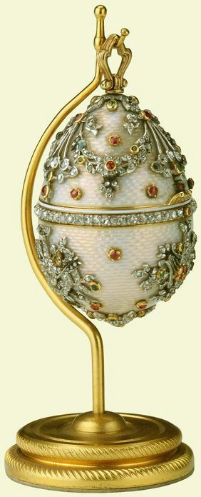 Egg, cream guilloché enamel set with diamond band around centre, upper section with ribbon swags, lower section with heart trophies, all set with rubies and emeralds, gold ring, hanging from plain gold stand, circular base with spiral pattern. Given to Queen Mary by her children (David, Bertie, Elizabeth, Mary and Harry Lascelles, Harry, George, Toria, Maud and Charles), Christmas 1927.