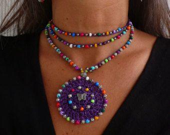 Este hermoso collar fue hecho a ganchillo con cuerda encerada azul añil, granos de cristal y abalorios de plata tibetanas. Pueden ser usado cerca de la nuca o más flojo, solo apretado lo quieras. El encaje es suficiente para envolver 2 veces alrededor del cuello. Cada extremo de la cadena es cerrada por con algunas perlas de vidrio, un tapón de grano de plata adornado y un grano de la semilla de acai. It´s uno de un tipo y se ven muy bien en verano o en invierno. Este collar de ganchillo es…