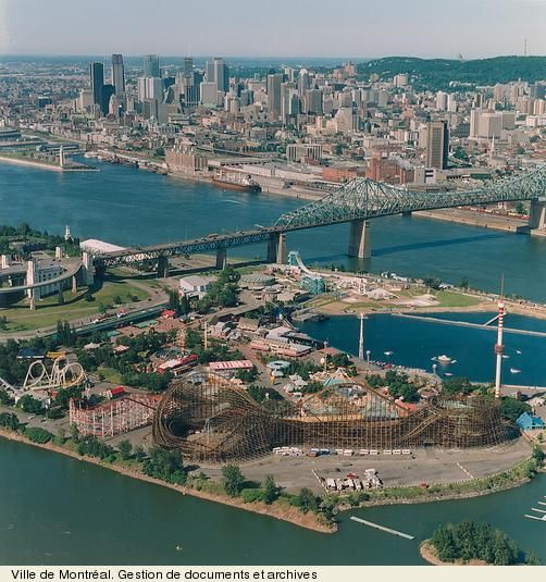 "Vue de la Ronde sur l'île Sainte-Hélène, du pont Jacques-Cartier et du centre-ville. - View of ""La Ronde"" amusement park, of the Jacques Cartier Bridge, and of downtown Montreal."