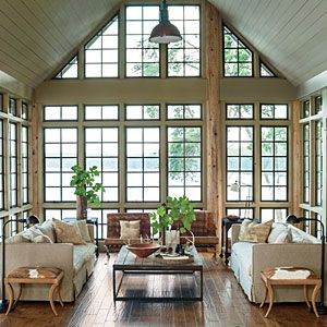 Lake House in the Trees | Panoramic Living Room | SouthernLiving.com; Like the windows, two ottomans covered with hide at the end of the sofas, the industrial coffee table, and low-key chairs