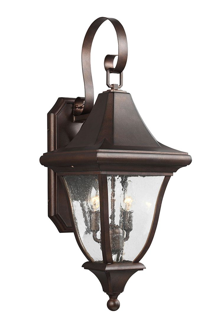 Oakmont 2 - Light Outdoor Wall Lantern by Feiss: Inspired by a beautiful church, the Oakmont lantern boasts incredible details, from the steeply pitched roof line and softly curved glass panels to an angular back-plate, lovely curved arm extension and classic finials. A new Patina Bronze finish paired with Clear Seeded glass give this stately collection old world charm. Wet Rated. Perfect for your porch or backyard.