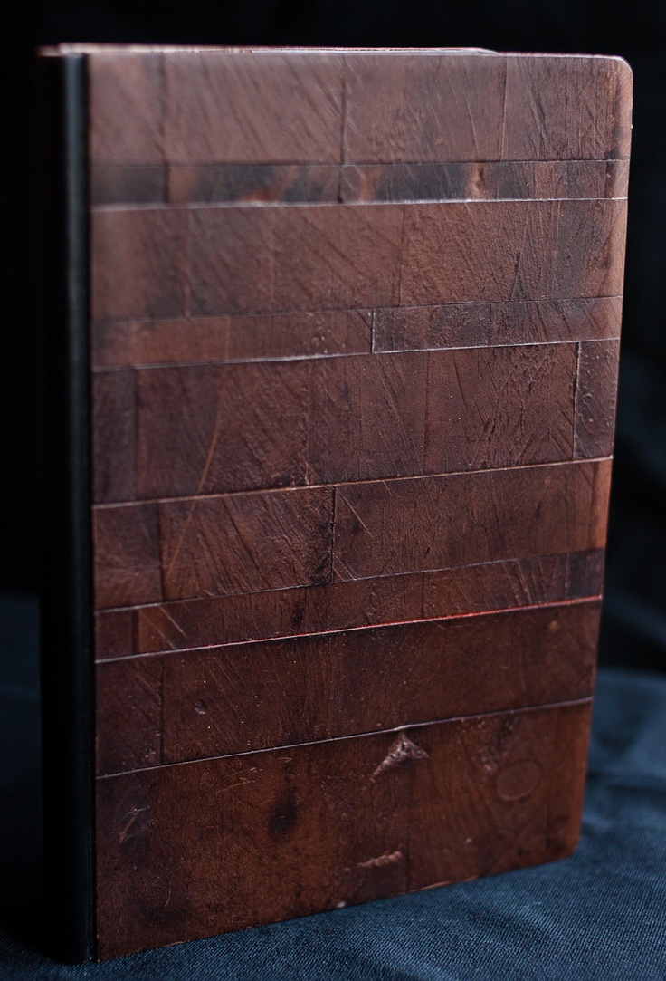 Refillable notebook, bradel binding. The interior is made of Hahnemühle paper. Outside is maroon calf stamped with wood of pallet to give it relief pattern. The back is of smooth black calf.