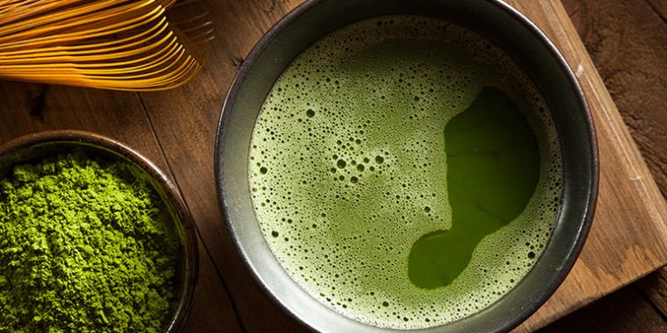 Bowl of matcha with matcha whisk and powdered matcha tea