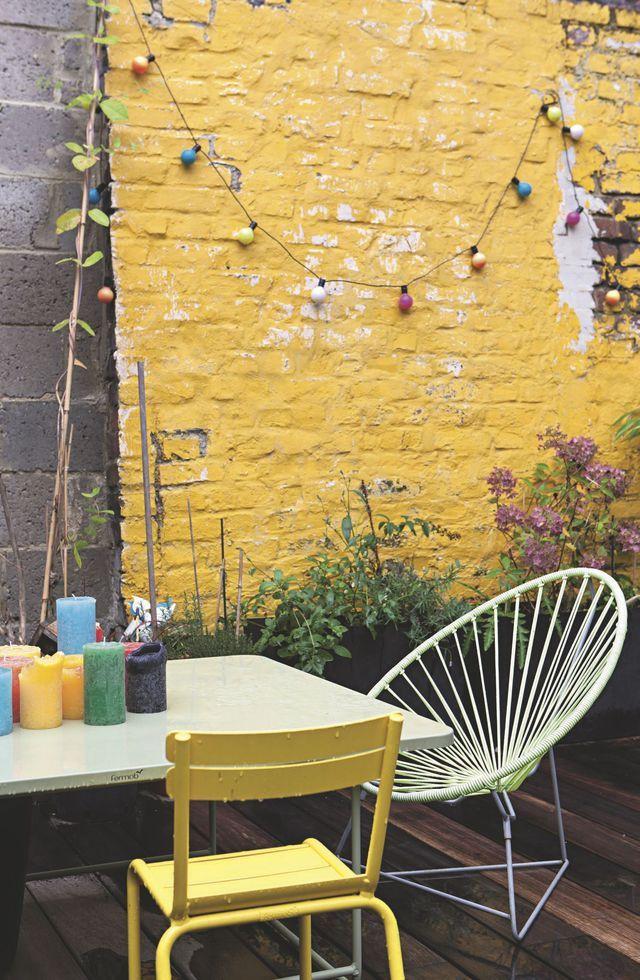 """Pour réveiller les mornes murs en briques, un coup de peinture jaune suffit ! Chaise Fermob ; fauteuil """"Acapulco"""", Boqa."""
