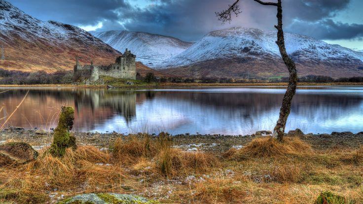 Скачать обои тучи, горы, снег, берег, развалины, Kilchurn Castle, замок, дерево, озеро, пасмурно, Шотландия, трава, камни, раздел пейзажи в разрешении 1920x1080