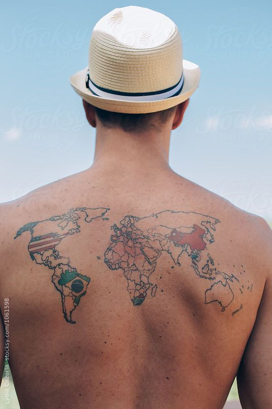 A young man with a tattoo on the back of the world map by Lydia Cazorla for Stocksy United
