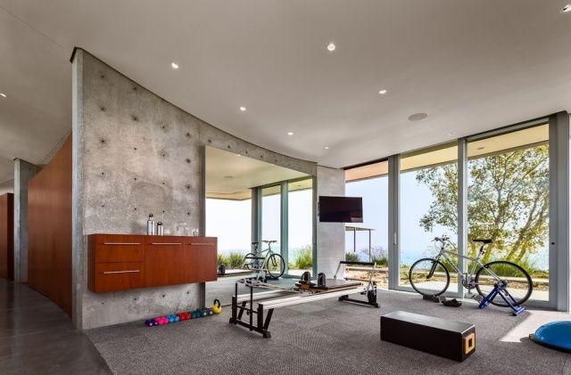 kleiner fitnessraum ausblick meer sichtbetonwand teppichboden