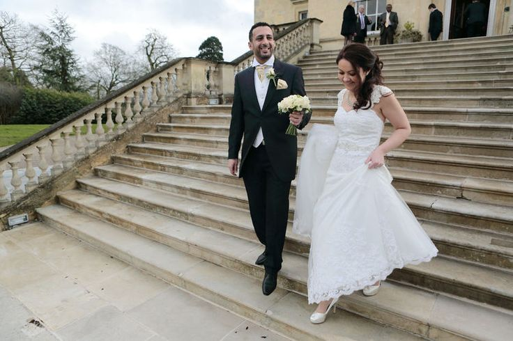Bride and groom walking down the steps outside this beautiful mansion house.