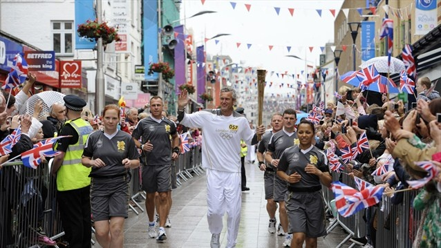 Olympic swimmer Mark Foster carries the Olympic Flame through the centre of Southend during Day 49 of the London 2012 Olympic Torch Relay.