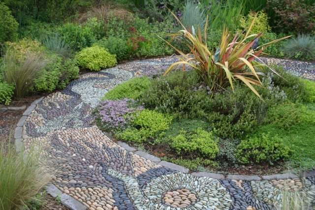 This very creative and beautiful walkway of different coloured stones is considered a mosaic. It is bordered with manufactured blocks on end. Picture compliments of www.american-stone.com