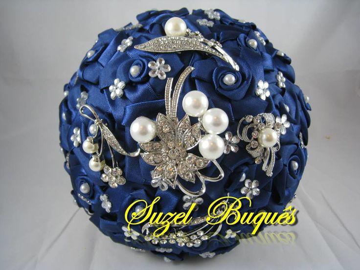 Buquê Azul Marinho c/ 5 Broches e Pérolas <br> <br>Lindo Buquê produzido com rosas super delicadas em Cetim no tom de Azul Marinho. <br> <br>Detalhes do Buquê: <br>*Pérolas em Todos os Miolos das Rosas. <br>* Florzinhas de strass, espalhadas pelo Buquê <br>* Fitas de cetim envolvendo a haste <br>* Laço de cetim, com uma delicada fita no Cabo. <br>* Strass no Cabo. <br>Os Buquês são personalizados conforme a sua escolha! <br> <br>* Verificar modelos e disponibilidade de Broches para…