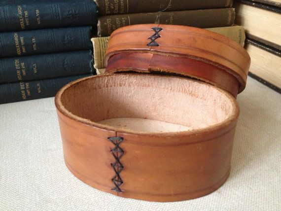 Vintage Handmade Tooled Leather Trinket Jewelry Box Made in England  Lovely natural colored leather with tooled accents, Very sweet and great for gifting jewelry too. Made with a thick piece of leather & handsewn.  Measures; 5 1/8 length, 3 7/8 width, approx. 3 height  In lovely vintage condition with some wear and fading from age. Interior is clean and free of odors. About a 1 gap on the bottom that needs re-gluing. Thanks for viewing.