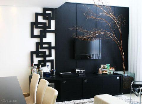 Para esse apartamento, o desafio era fazer um ambiente estiloso e aconchegante, por isso foi escolhido como piso o porcelanato e para o painel principal o MDF madeirado texturizado. Tons de preto, prata e branco equilibram o espaço. Projeto de Carola Cunha.