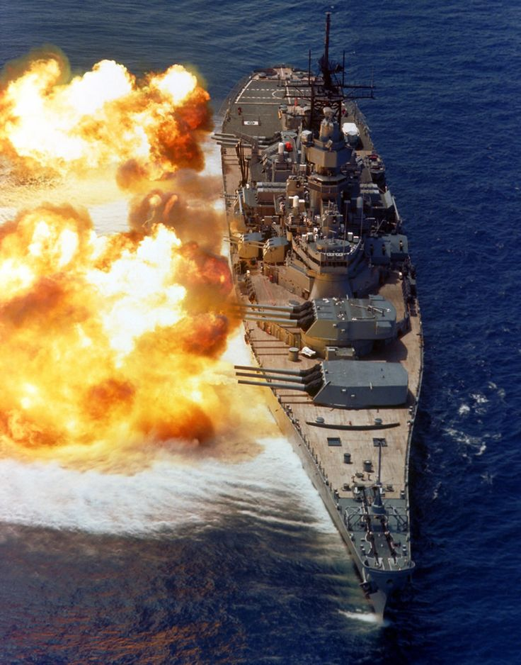 An overhead view of the battleship USS IOWA (BB-61) firing all 15 of its guns (nine 16-inch and six 5-inch) during a target exercise near Vieques Island.