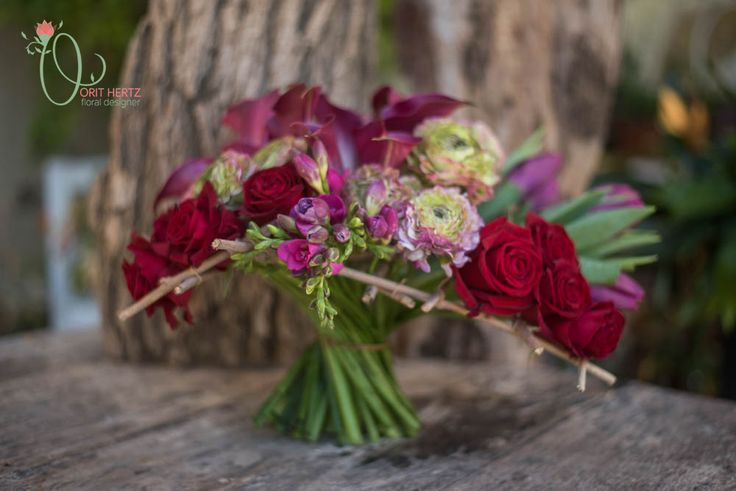 Romantic and deep colored flowers in this hand tied bouquet framed with twigs.
