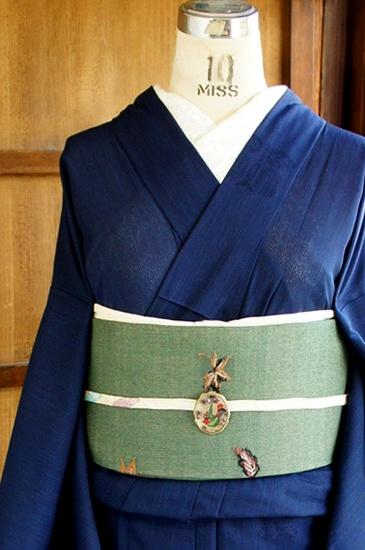 藍を重ねたような深く沈んだ濃藍色に遠州椿の透かし模様がぽんぽんと散らされた絽の夏着物です。