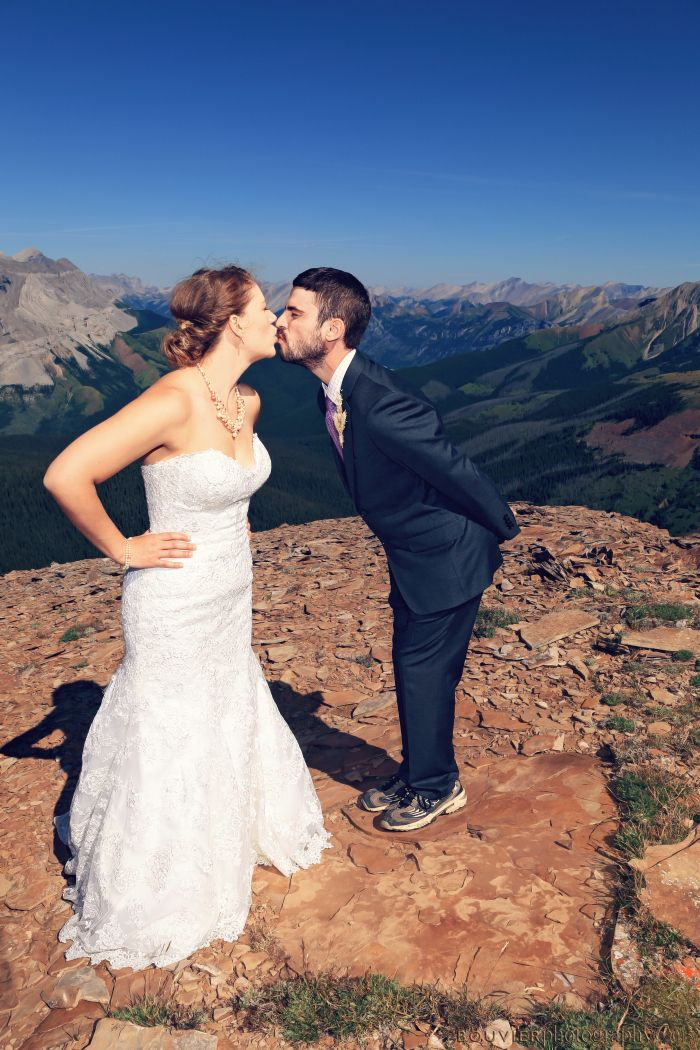 Bride & groom sharing a kiss on the mountain top in Canmore, Alberta. Summer heli-wedding. Silly wedding kiss. Canmore Alberta wedding.