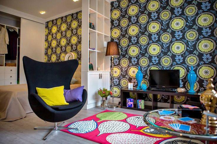 Цветовая гамма интерьера построена на контрасте нейтральных светлых оттенков и ярких акцентов в виде обоев с цветочным принтом и аксессуаров. Черное кресло с разноцветными подушками, яркий ковер и обилие цветов делают квартиру жизнерадостной