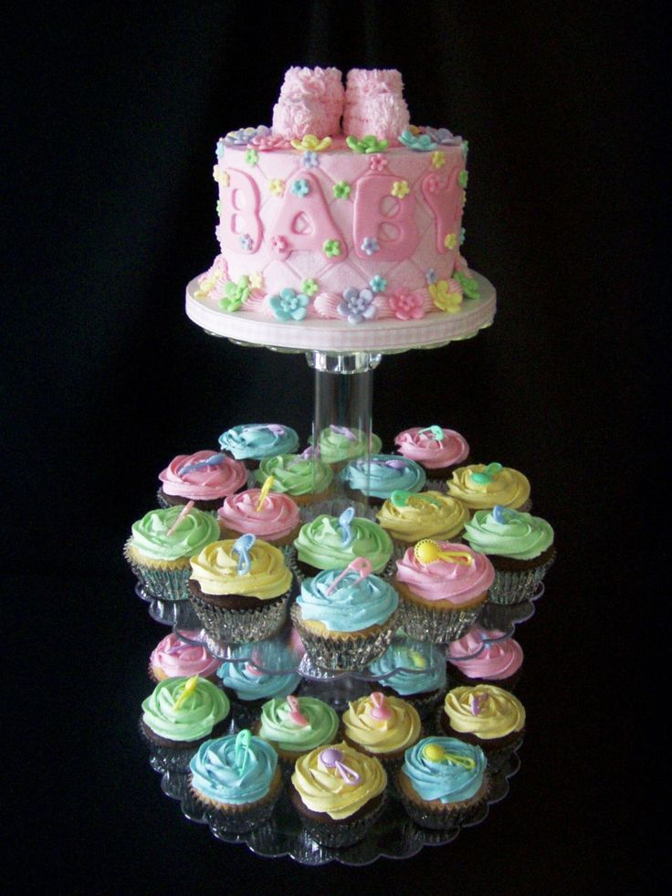 """Baby Shower Cupcakes - This is a 6"""" cake w/cupcakes to match. I bought the little plastic rattles and diaper pins at a Dollar Tree store and wanted to incorporate those colors in the cake so I made the multi-colored fondant flowers for this reason. Booties on cake are made from marshmallows."""