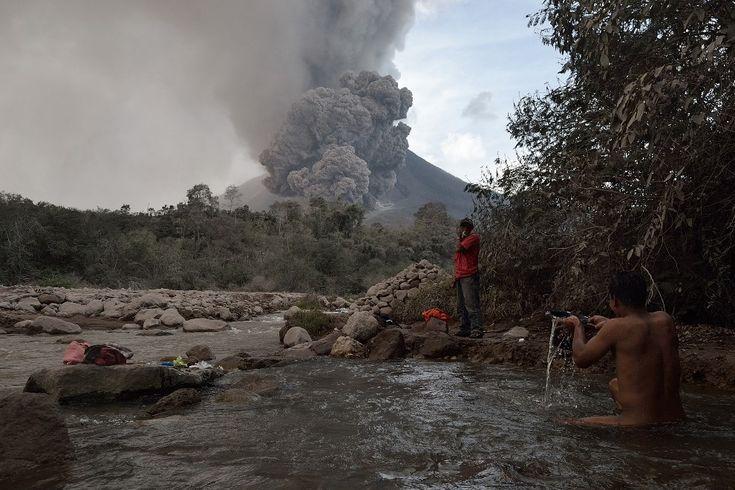 21.01.2014 r., Indonezja, Karo: Mieszkaniec pobliskiej wioski kąpie się w rzece (w tle erupcja wulkanu  Sinabung). AFP PHOTO / SUTANTA...