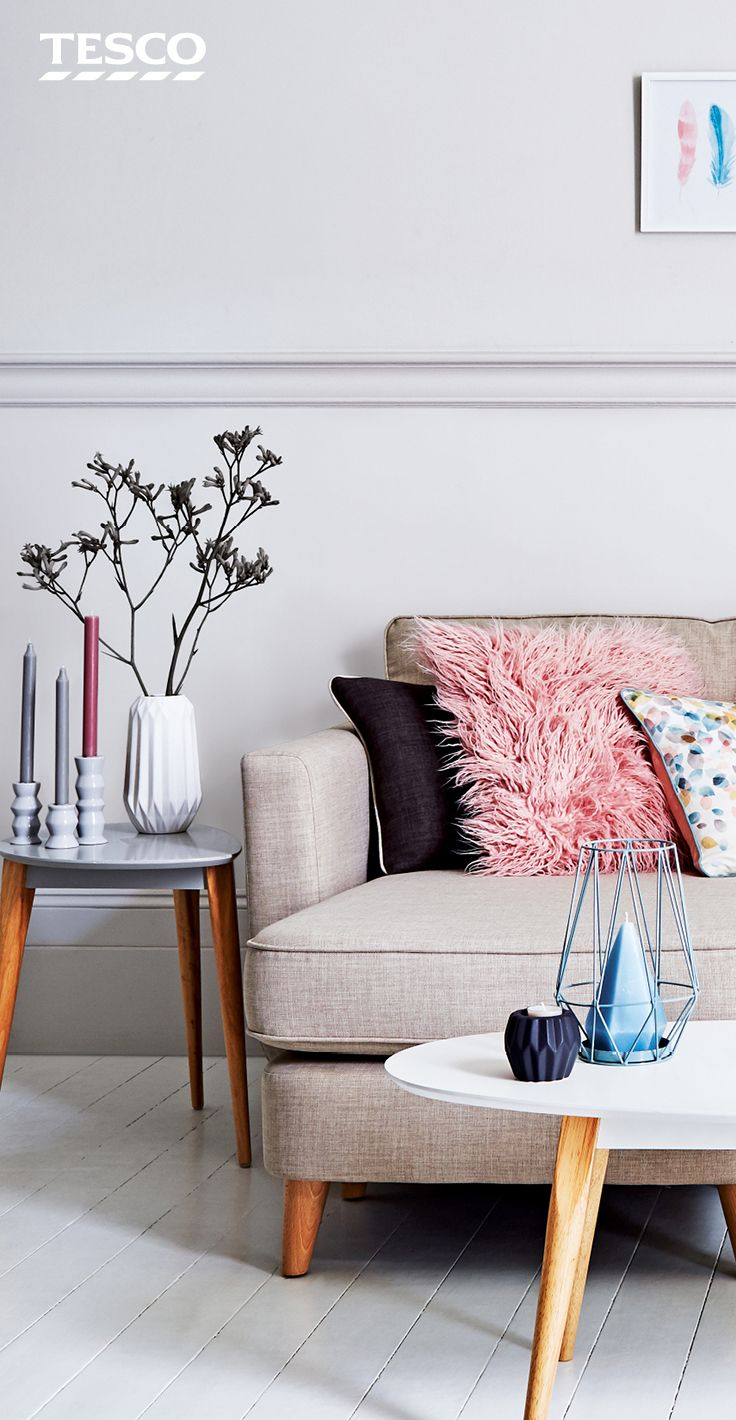 For a simple, contemporary living room, accessorise with pink faux fur cushions and set a white coffee table with textured vases and blue candles. | Tesco