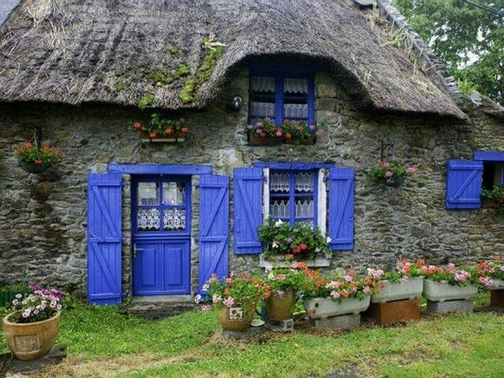 Sweet little thatched roof stone cottage with with cornflower blue shutters, door and trim. Cali's Cornflower Cottage