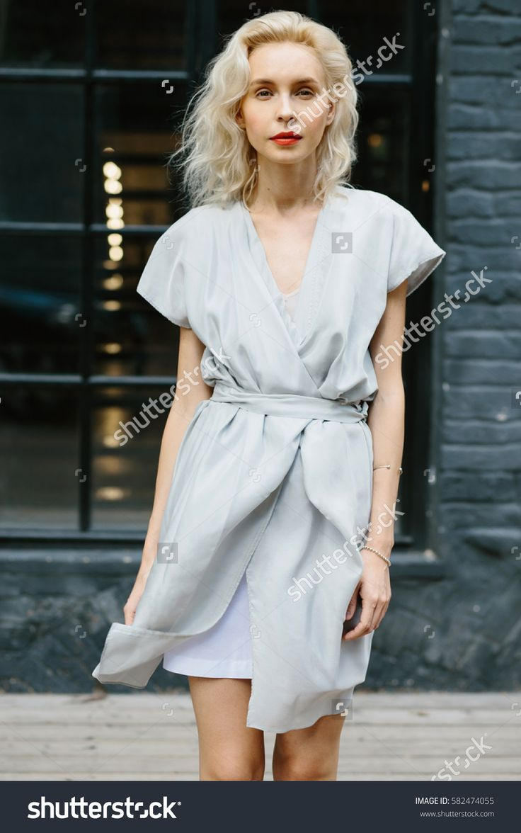 Portrait of young beautiful blonde woman in Asian style blue trendy dress posing outside in the city streets.